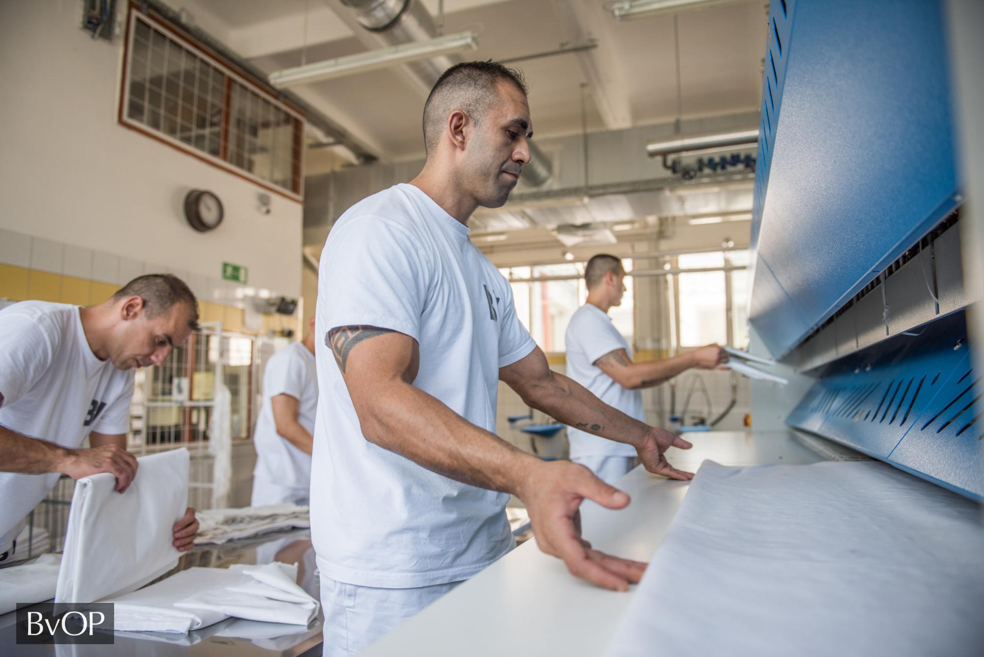 Fogvatartottak hajtogatják a tiszta ruhát a börtönmosodában